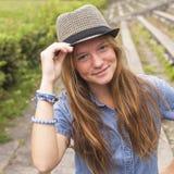 Muchacha adolescente linda que lleva un sombrero, al aire libre en el parque Fotos de archivo