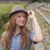 Muchacha adolescente linda que lleva un sombrero, al aire libre en el parque (series cuadradas) caminata Fotos de archivo