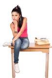 Muchacha adolescente linda que se sienta en su escritorio Imagen de archivo