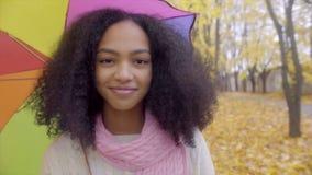 Muchacha adolescente linda que sonríe con el paraguas del color en parque del otoño metrajes