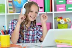 Muchacha adolescente linda que usa el ordenador portátil Imagenes de archivo