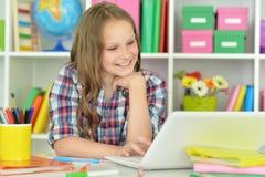 Muchacha adolescente linda que usa el ordenador portátil Imágenes de archivo libres de regalías