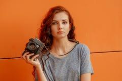 Muchacha adolescente meditativa con la cámara del vintage en manos Fotografía de archivo