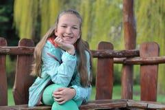 Muchacha adolescente moderna que se sienta en el banco de madera Imagen de archivo