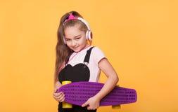 Muchacha adolescente moderna que sostiene el monopatín sobre fondo amarillo Imágenes de archivo libres de regalías