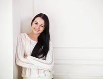 Muchacha adolescente morena feliz cerca de la pared en el cuarto Imágenes de archivo libres de regalías