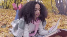 Muchacha adolescente negra linda con el álbum del dibujo en bosque del otoño almacen de metraje de vídeo