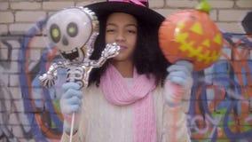Muchacha adolescente negra linda en el sombrero de la bruja que presenta caras en Halloween almacen de video