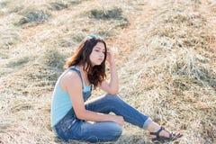 Muchacha adolescente pensativa en un campo con el str Fotografía de archivo