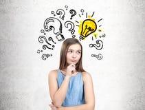 Muchacha adolescente pensativa en un vestido, preguntas y un bulbo Fotos de archivo
