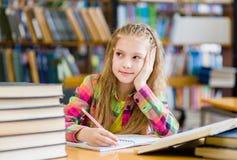 Muchacha adolescente pensativa en una biblioteca Foto de archivo libre de regalías