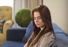 Muchacha adolescente pensativa que se relaja en el sofá Imagen de archivo