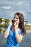 Muchacha adolescente preciosa con entusiasmo que habla en el teléfono y que recibe noticias y sorpresa alegres Imagen de archivo