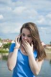 Muchacha adolescente preciosa con entusiasmo que habla en el teléfono y que recibe sorpresa Fotografía de archivo libre de regalías