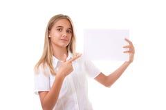 Muchacha adolescente preciosa en la camisa blanca que señala en el tablero de la muestra de publicidad, aislado Imagen de archivo libre de regalías
