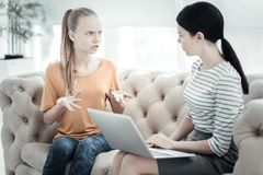 Muchacha adolescente preocupada que explica sensaciones al psicólogo de sexo femenino Imagen de archivo