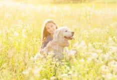 Muchacha adolescente que abraza su golden retriever Imagen de archivo libre de regalías