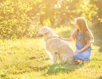 Muchacha adolescente que abraza su golden retriever Imagenes de archivo