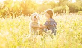 Muchacha adolescente que abraza su golden retriever Fotografía de archivo