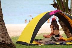 Muchacha adolescente que acampa y que se relaja cerca de la tienda en el beac del coco Fotografía de archivo libre de regalías