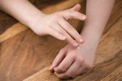 Muchacha adolescente que aplica la crema de la mano Fotos de archivo libres de regalías
