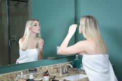 Muchacha adolescente que aplica maquillaje Fotografía de archivo
