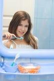 Muchacha adolescente que aplica sus dientes con brocha Imagenes de archivo