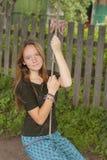 Muchacha adolescente que balancea en un oscilación de la cuerda en el campo Naturaleza Fotografía de archivo libre de regalías