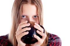 Muchacha adolescente que bebe de la taza Fotografía de archivo