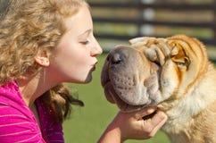Muchacha adolescente que besa un perro Fotografía de archivo