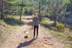 Muchacha adolescente que camina con un perro blanco en bosque Imágenes de archivo libres de regalías
