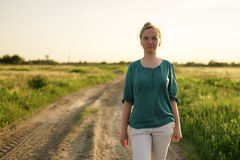 Muchacha adolescente que camina en el camino rural de la suciedad entre los campos Fotografía de archivo libre de regalías