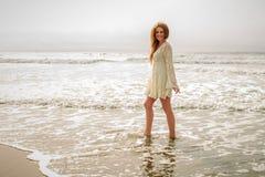 Muchacha adolescente que camina en el océano Imagenes de archivo