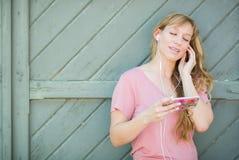 Muchacha adolescente que canta adelante a la música en su Smartphone Fotos de archivo