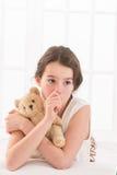 Muchacha adolescente que celebra cariñosamente chupar del oso de peluche Imagen de archivo libre de regalías