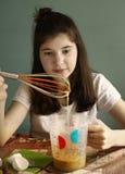 Muchacha adolescente que cocina la torta del plátano Imagen de archivo libre de regalías