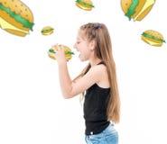 Muchacha adolescente que come las hamburguesas, hamburguesas alrededor de ella Foto de archivo libre de regalías