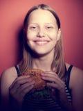 Muchacha adolescente que come una hamburguesa Foto de archivo