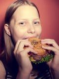 Muchacha adolescente que come una hamburguesa Fotos de archivo