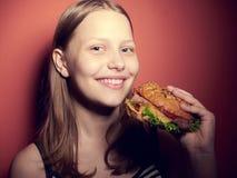Muchacha adolescente que come una hamburguesa Imagen de archivo
