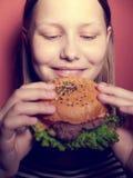Muchacha adolescente que come una hamburguesa Imagenes de archivo