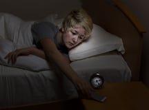 Muchacha adolescente que comprueba el teléfono celular tarde en la noche mientras que en cama Imágenes de archivo libres de regalías