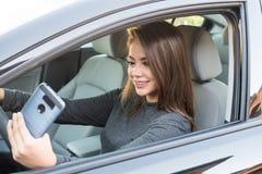 Muchacha adolescente que conduce el coche mientras que manda un SMS Fotos de archivo