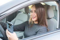 Muchacha adolescente que conduce el coche mientras que manda un SMS Foto de archivo