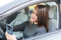Muchacha adolescente que conduce el coche mientras que manda un SMS Foto de archivo libre de regalías