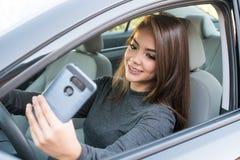 Muchacha adolescente que conduce el coche mientras que manda un SMS Imagenes de archivo