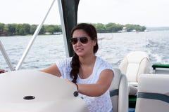 Muchacha adolescente que conduce un barco Fotos de archivo