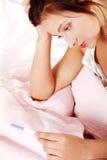 Muchacha adolescente que controla la prueba embarazada. Fotografía de archivo