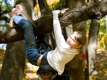 Muchacha adolescente que cuelga en el árbol Fotos de archivo libres de regalías