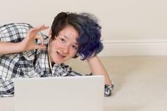 Muchacha adolescente que da la muestra aceptable mientras que en casa en el ordenador Imagen de archivo libre de regalías